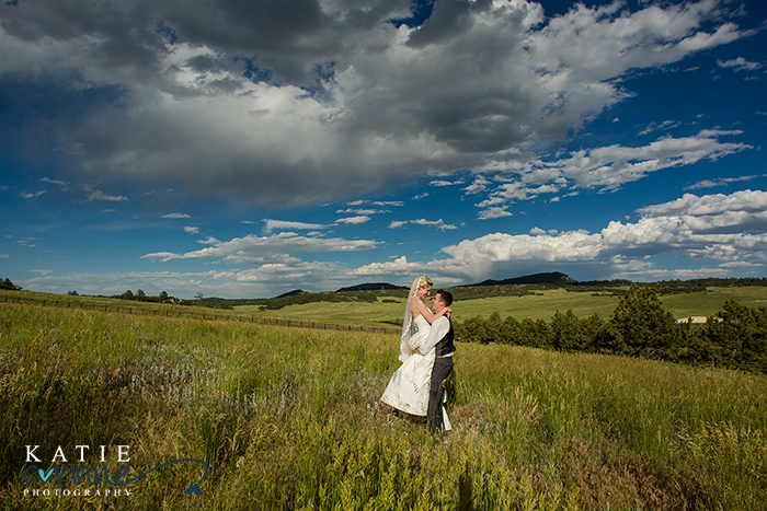 Couple in lush field and amazing blue sky in each other's arms. This bride and groom are so adorable and cute in the pasture.